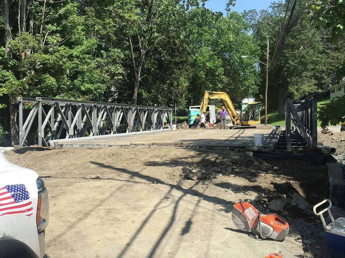 Crews work on the temporary bridge Wednesday Aug. 25, 2021 in the town of Sand Lake, N.Y. This span will take the place of the once destroyed in the July flooding.