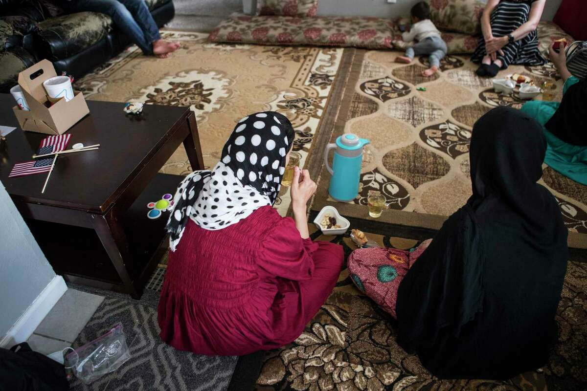 """Family members of """"Khan,"""" an Afghan Special Immigrant Visa holder, have tea as they settle into an apartment after fleeing the Taliban in Afghanistan on Monday, Aug. 23, 2021 in Houston. Some other arriving Afghans will not be Special Immigrant Visa holders, officials said."""