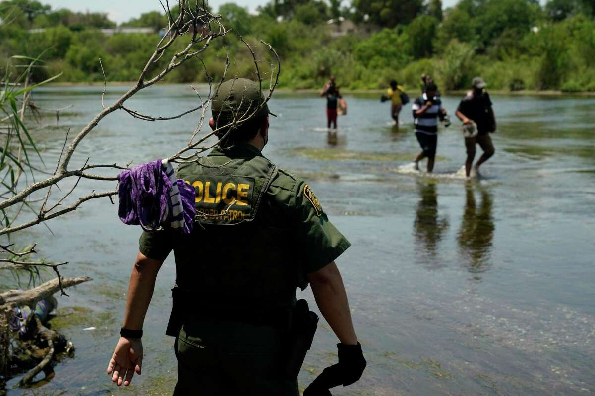 FILE - In this June 15, 2021, file photo a Border Patrol agent watches as a group of migrants walk across the Rio Grande on their way to turn themselves in upon crossing the U.S.-Mexico border in Del Rio, Texas. The Biden administration proposed Wednesday, Aug. 18, to change the way asylum claims are handled, aiming to cut a huge backlog of cases from the Southwest border that has resulted in people waiting years to find out if they will be allowed to stay in the U.S. (AP Photo/Eric Gay, File)