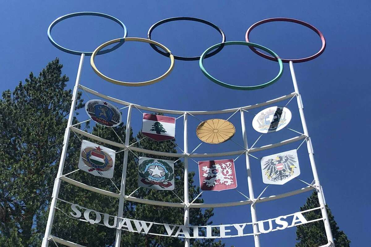 In this July 8, 2020 photo, the Olympic rings stand atop a sign at the entrance to the Squaw Valley Ski Resort in Olympic Valley.
