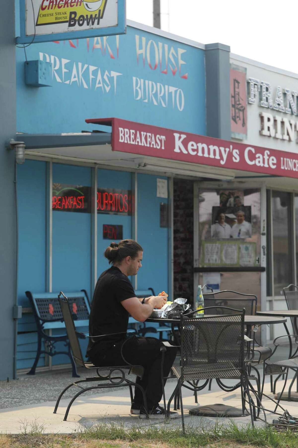 Christian Cusella of Campbell sits in front of Kenny's Cafe while enjoying his lunch.