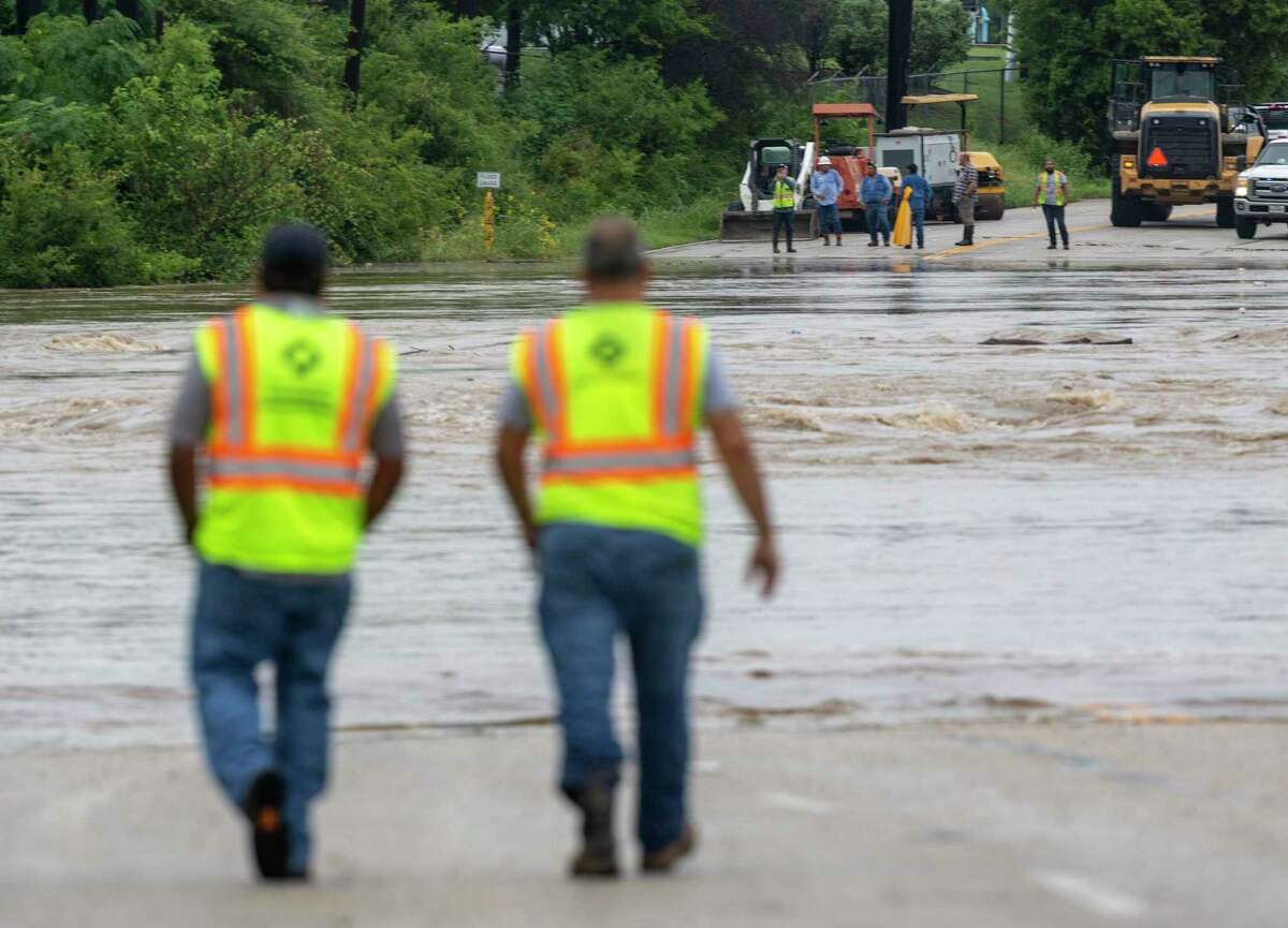 San Antonio Public Works employees check Leon Creek Tuesday, July 6, 2021 as it floods over West Commerce Street on the city's west side after the area saw multiple inches of rain in the last 24 hours. As of 10:00 a.m. the Austin/San Antonio National Weather Service office issued a flood warning for Leon Creek At I-35. The NWS also issued a major flood warning for the San Antonio river in areas including Elmendorf and Floresville.