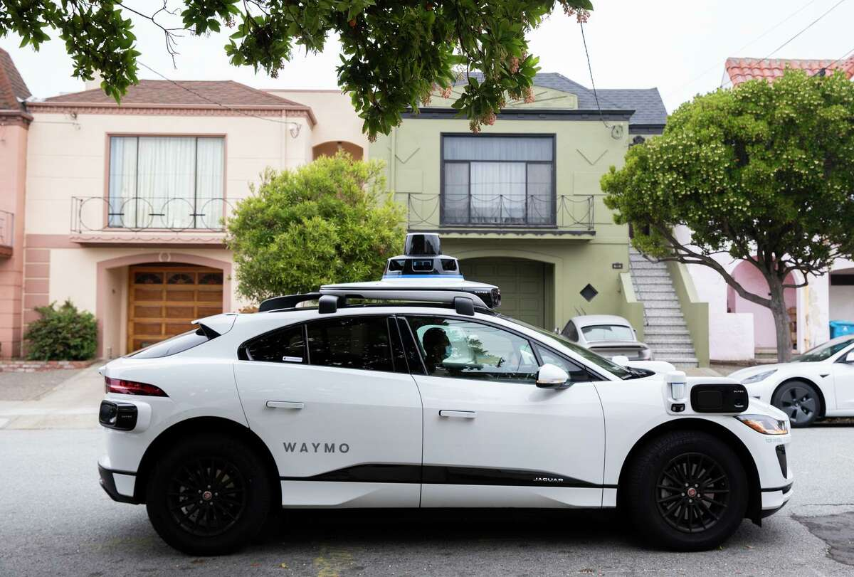A Waymo robot taxi arrives to pick up passengers during a demonstration ride in the Sunset District.