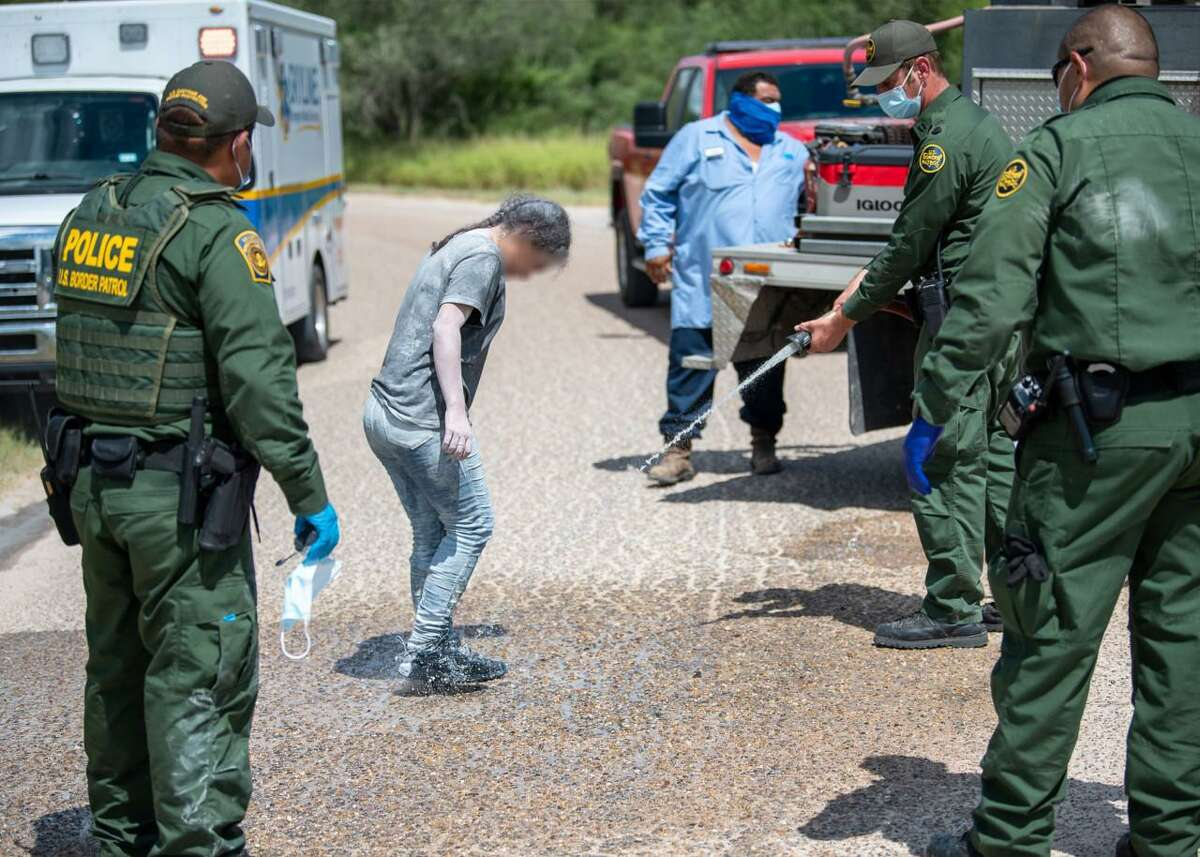 U.S. Border Patrol agents decontaminate a migrant who was found covered in powdered clay during a human smuggling attempt.