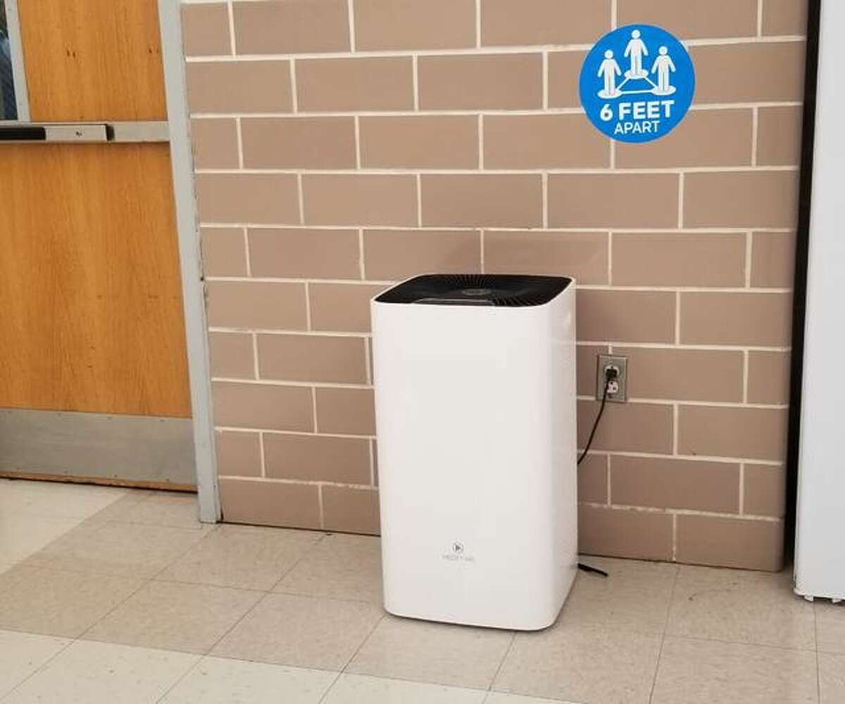 A HEPA filtration unit is connected in a school cafeteria. The HEPA filtration system is installed in cafeterias where six feet of distance is not possible.