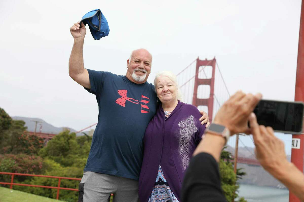 James Morrison (left) and Julie Morrison of Cypress get their photo taken by Anna Simpson of Albany, New York as they visit the Golden Gate Bridge during a trip to San Francisco in August. Tourist numbers for the city are up from last year, but still well below 2019 marks.