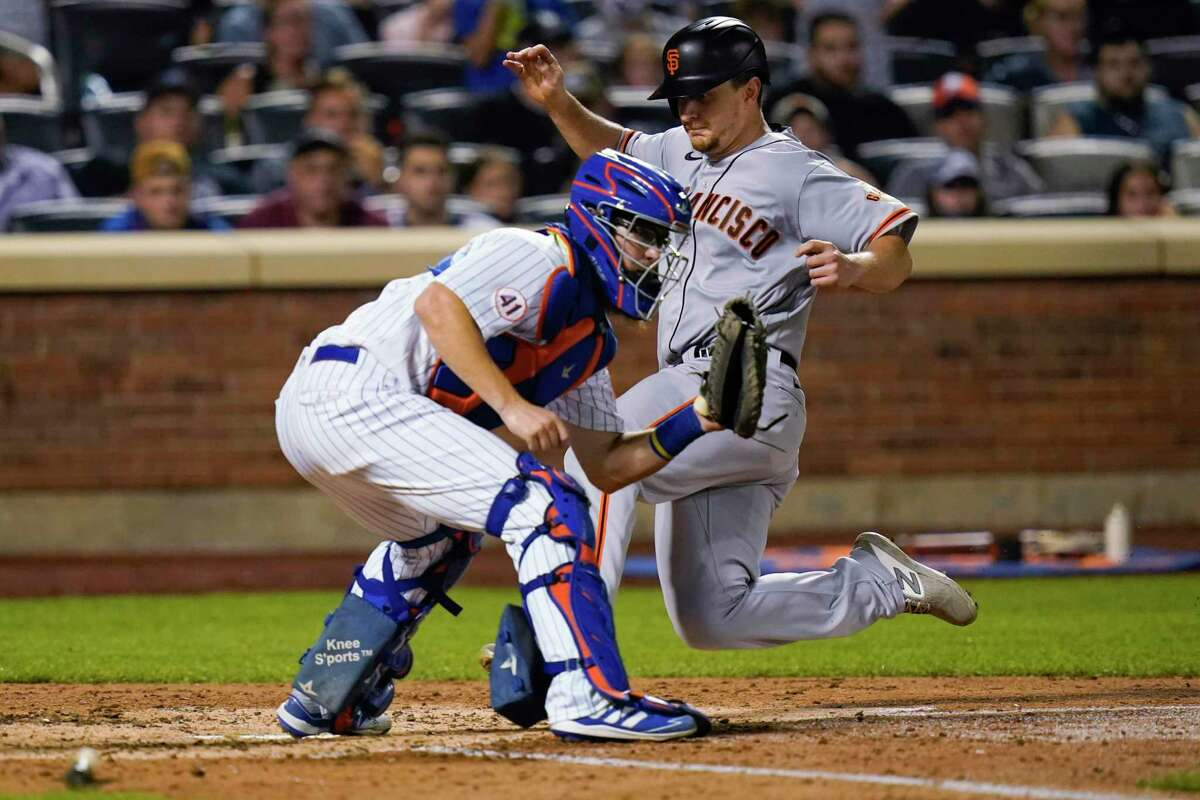 San Francisco Giants' Alex Dickerson, right, scores New York Mets catcher Patrick Mazeika on a double by Brandon Crawford during the seventh inning of a baseball game Wednesday, Aug. 25, 2021, in New York. (AP Photo/Frank Franklin II)
