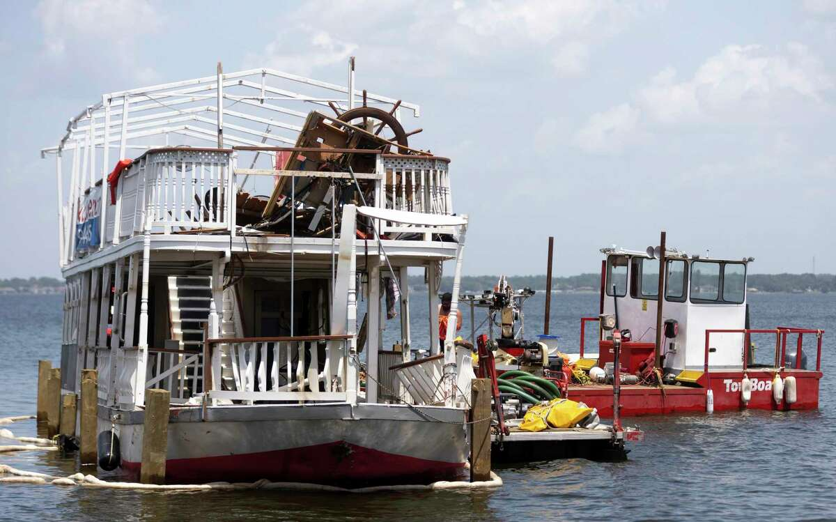 The Lake Conroe Queen is seen being hitched to the back of a tow boat by Lewis Towing & Salvage, Friday, Aug. 20, 2021, in Lake Conroe. The Lake Conroe Queen capsized Saturday near Regency Point during a thunderstorm.