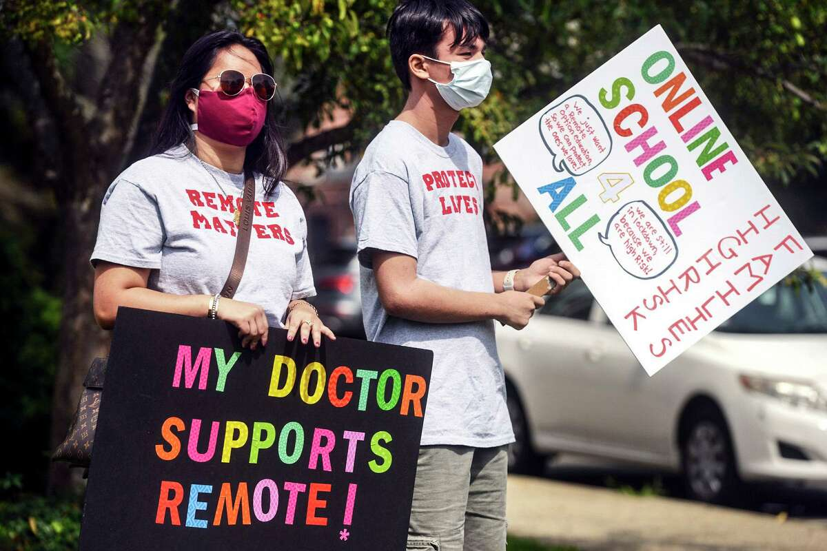 Macy Schulman, left, and Mason Yeoh, both students at Fairfield Warde High School, carry pro-remote learning signs during a rally of parents and students fighting to have an online option for school this year, Monday, Aug. 16, 2021, in Fairfield, Conn. (Ned Gerard/Hearst Connecticut Media)