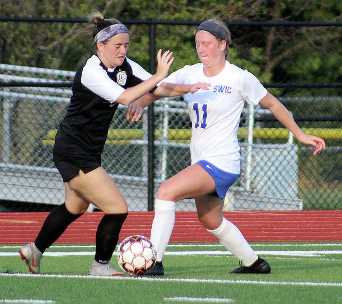 Southwestern Illinois College's Maggie Evans, a sophomore from Alton, pokes the ball away from LCCC's Natalie Black, a freshman from Triad, during action Wednesday night at Belleville Althoff.