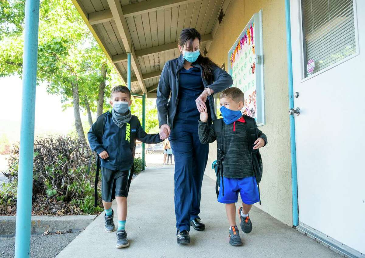Marin checks her watch as she takes her sons, Maverick (left) and Maddox, to school before heading to work at the hospital.