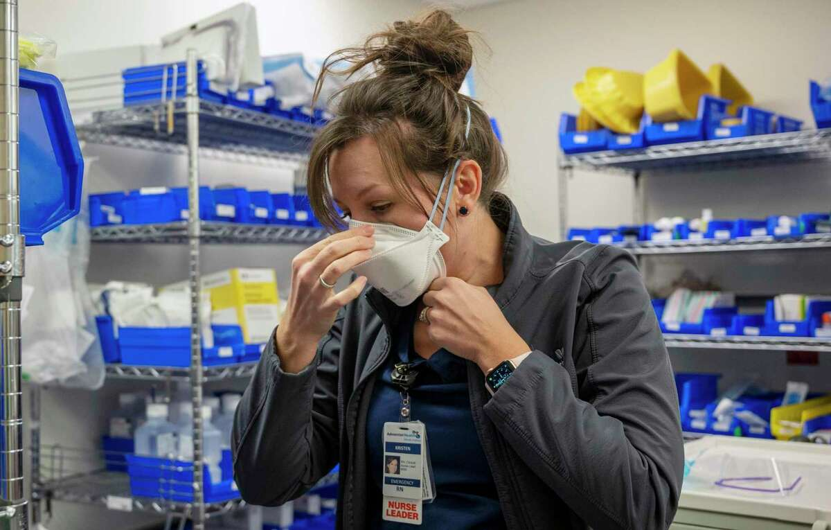 Registered nurse Kristen Marin puts on a N95 mask when she arrives at Adventist Health Ukiah Valley Hospital on Wednesday. Experts say N95s are the best bet for protection against both the delta variant and wildfire smoke.