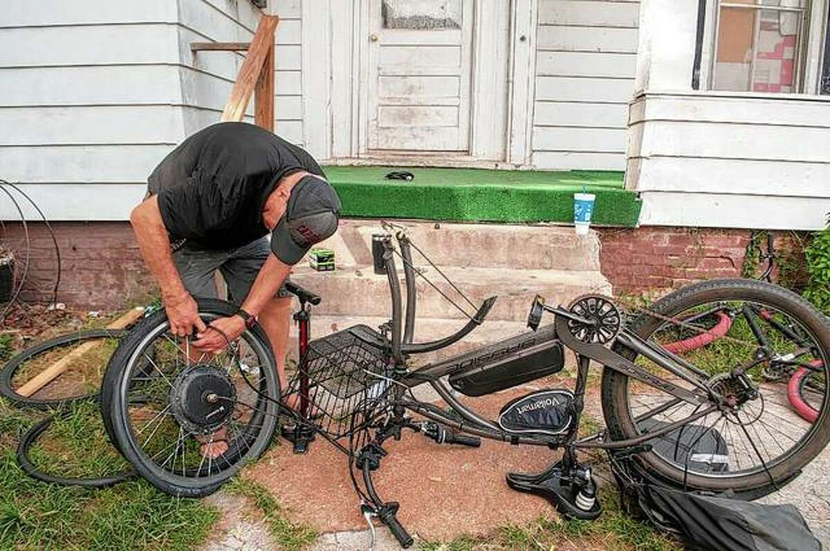 Rodney Coats braves Wednesday's heat to replace an inner tube and tire on the front wheel of a bicycle on State Street. The Jacksonville area remains under a heat advisory through 7 p.m. today, with the heat index expected to reach near 105 degrees for the fourth day in a row.