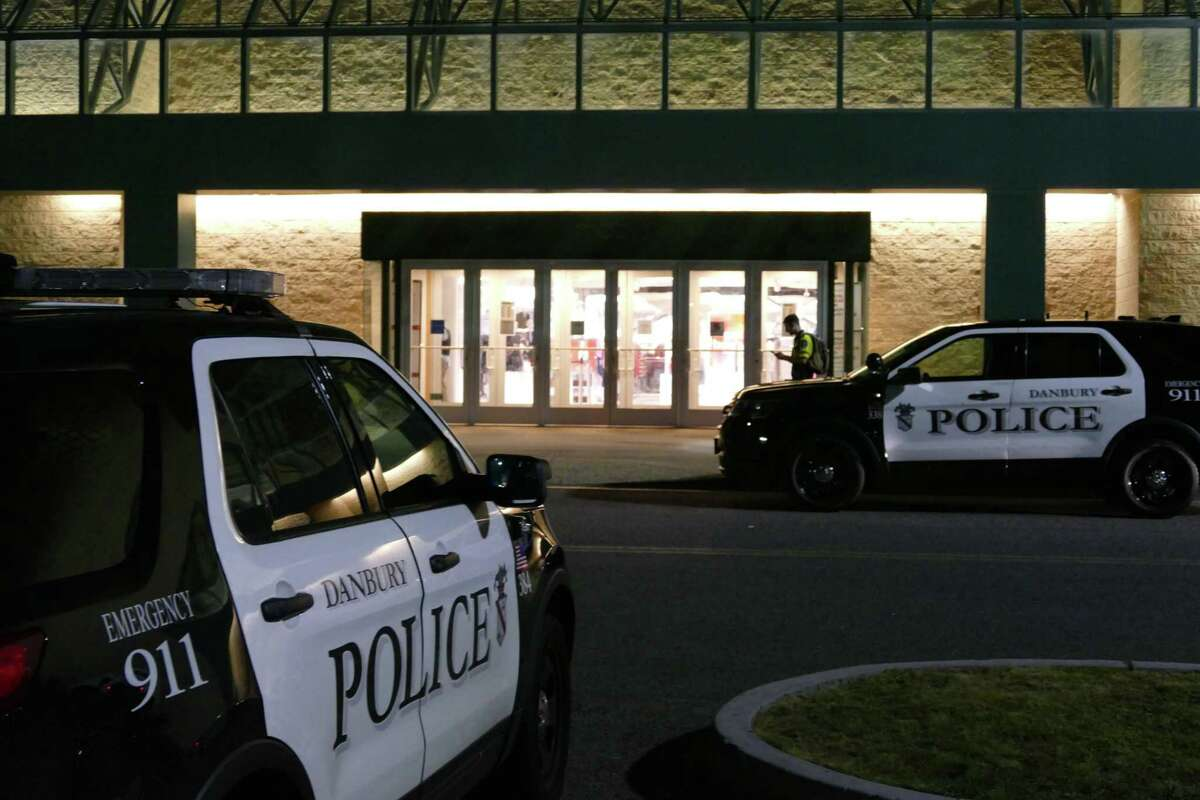 People wait outside the Danbury Fair Mall in Danbury, Conn. on Wednesday, Aug. 11, 2021 after the shooting of a 15-year-old girl locked the mall down.