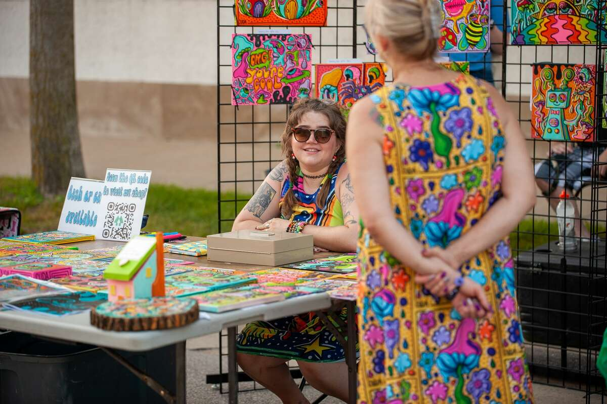 Alex Bearinger, owner of Cudabera Fine Art & Photo, has a chat during the Fire Culture Event onAug. 25, 2021 in Downtown Midland.