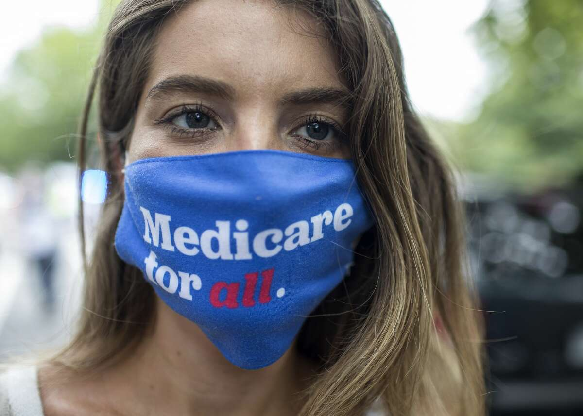 A woman wearing a face mask with Medicare for all written on it. (Photo by Probal Rashid/LightRocket via Getty Images)