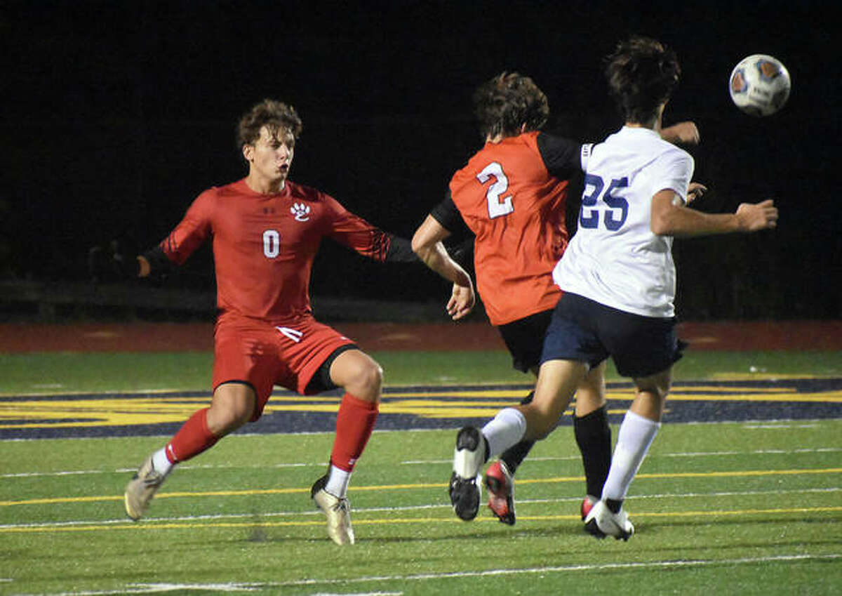Edwardsville defender Jake Duboise clears the ball away from Althoff's Hank Gomric as keeper Nathan Beck comes out on the play in the second half on Wednesday in Belleville.