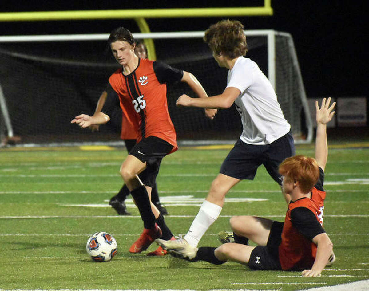 Edwardsville's Sam Reader collects the ball after a challenge between an Althoff player and Edwardsville's Berick Selberg in the second half.