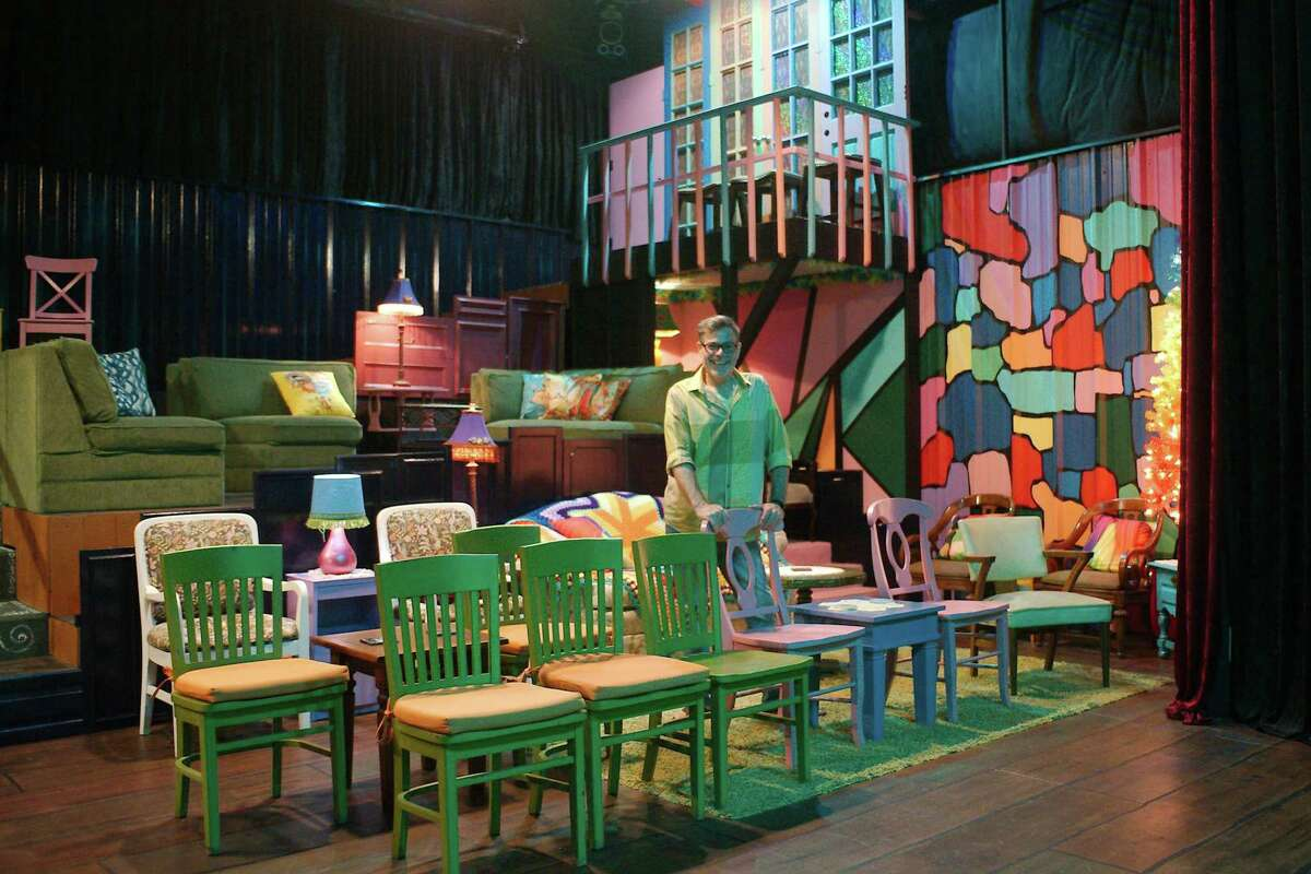 Jordan stands in the seating gallery of the the Red Door Theater Company, marked by nontraditional seating and eclectic design elements.