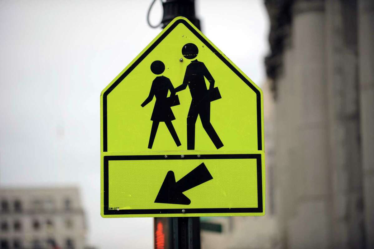A traffic sign alerts motorists to a pedestrian crossing in Lower Manhattan, New York City. (Photo by STAN HONDA/AFP via Getty Images)