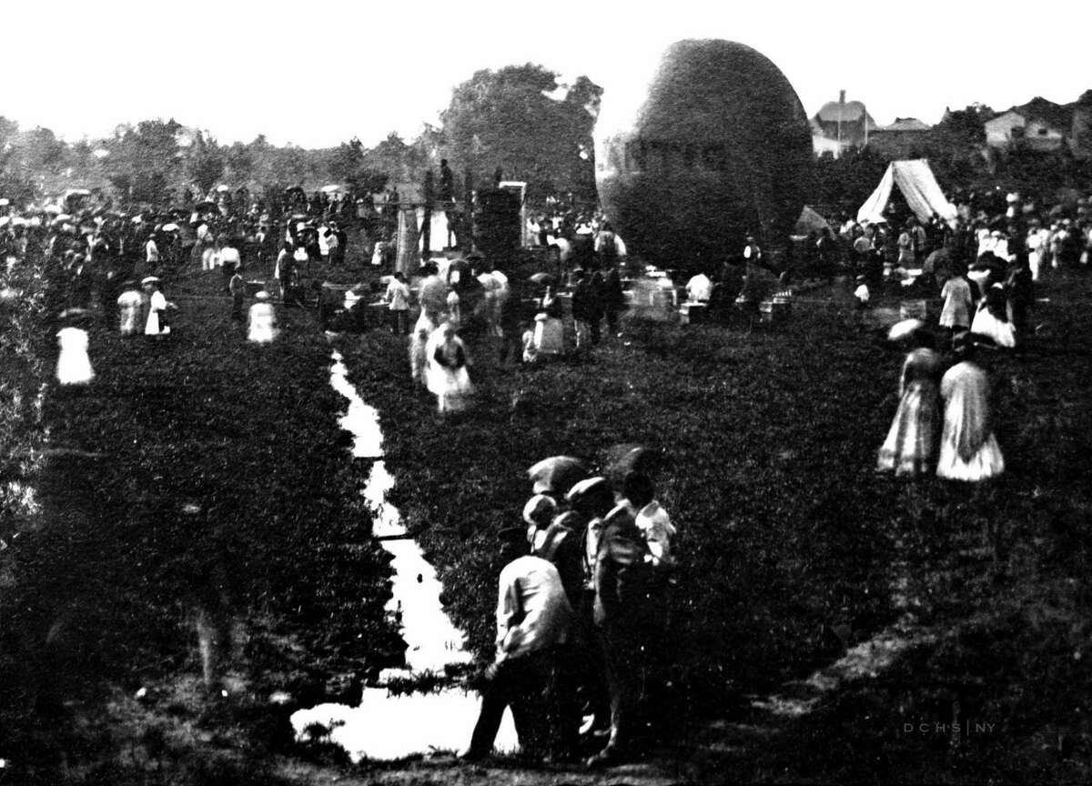 """Nellie Thurston and Herman Squire each took off from Eastman Park in Poughkeepsie on July 4, 1871. In this historic photo of the day, crowds are gathered to watch the feat. Squire's balloon """"Atlantic"""" can be seen in the background."""