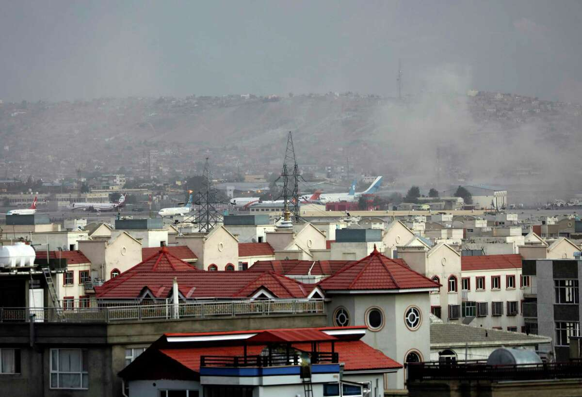 Smoke rises from a deadly explosion outside the airport in Kabul, Afghanistan on Thursday. Two suicide bombers and gunmen targeted crowds trying to get on a flight in the waning days of a massive airlift that has drawn thousands of people seeking to flee the Taliban takeover. (AP Photo/Wali Sabawoon)