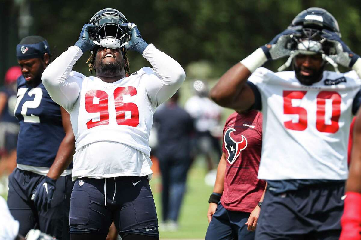 Houston Texans defensive tackle Vincent Taylor (96) and defensive end Jordan Jenkins (50) don their helmets during an NFL training camp football practice Thursday, Aug. 26, 2021, in Houston.