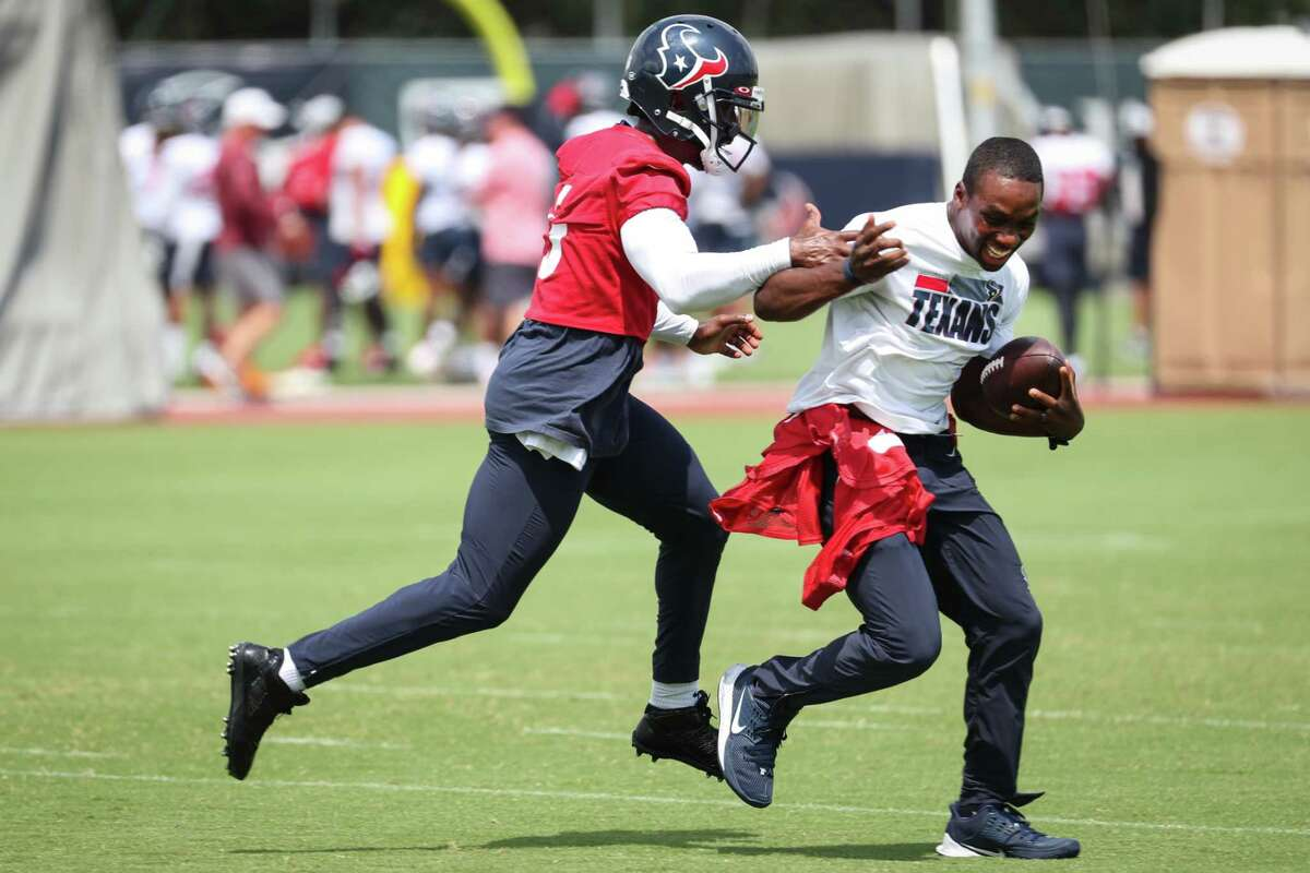Houston Texans quarterback Tyrod Taylor (5) chases down offensive assistant coach DeNarius McGhee during an NFL training camp football practice Thursday, Aug. 26, 2021, in Houston.