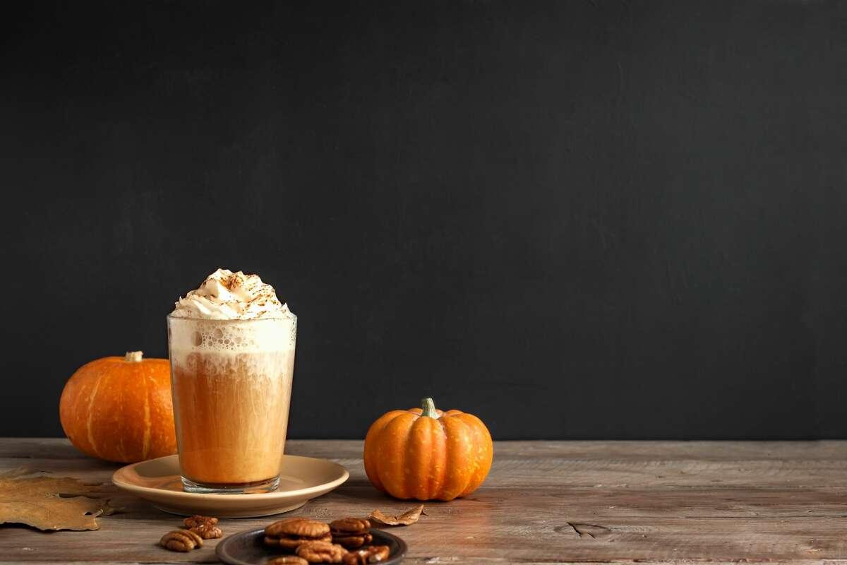 Pumpkin spice latte. Seasonal coffee drink and organic pumpkins near black wall, copy space.