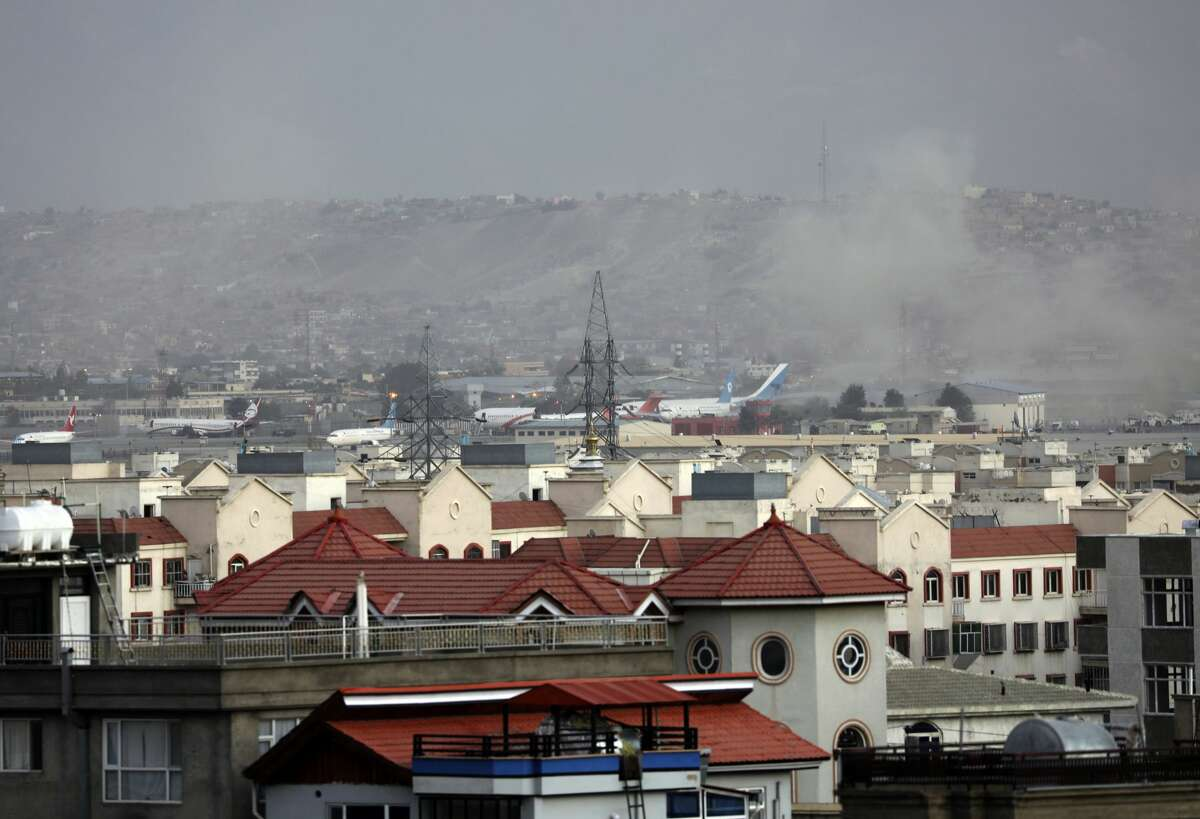 Smoke rises from a deadly explosion outside the airport in Kabul, Afghanistan, Thursday. Two suicide bombers and gunmen have targeted crowds massing near the Kabul airport, in the waning days of a massive airlift that has drawn thousands of people seeking to flee the Taliban takeover of Afghanistan. (AP Photo/Wali Sabawoon)