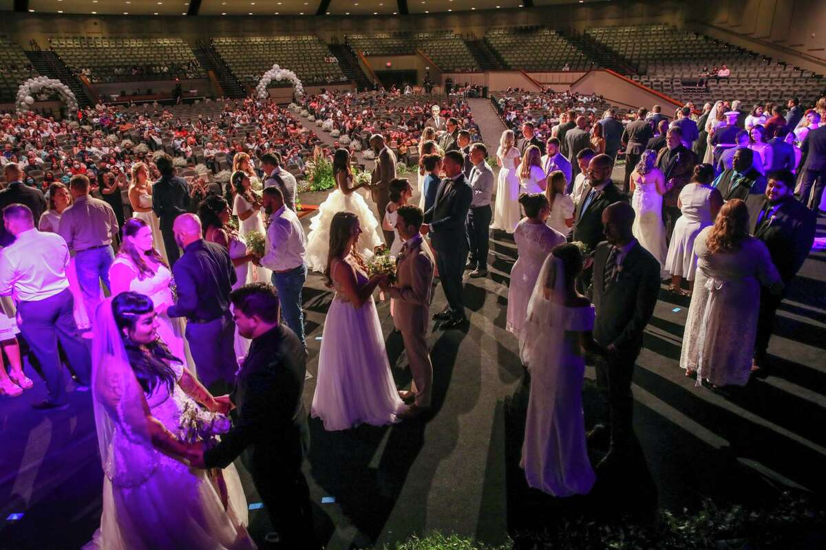 """Fifty-two couples say """"I do"""" at Community Bible Church on Saturday. Pastor Ed Newton had challenged the men in his congregation to """"to put a ring on her finger."""""""