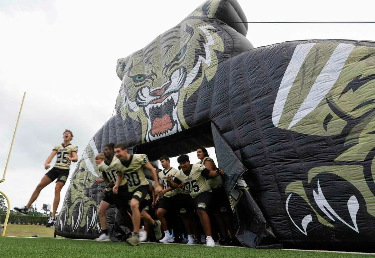Conroe football players take the field during Meet the Tigers at Moorhead Stadium, Friday, Aug. 6, 2021, in Conroe. Community members saw performances by the Conroe High School's band, Golden Girls, cheerleaders and stayed to watch the football team practice under the lights.