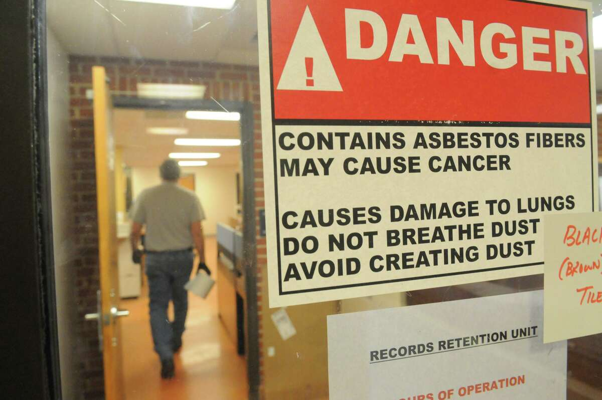 Signs warning of asbestos posted throughout the Stamford Police Station in Stamford, Conn., Dec. 12, 2014. What to do with the property is being debated.