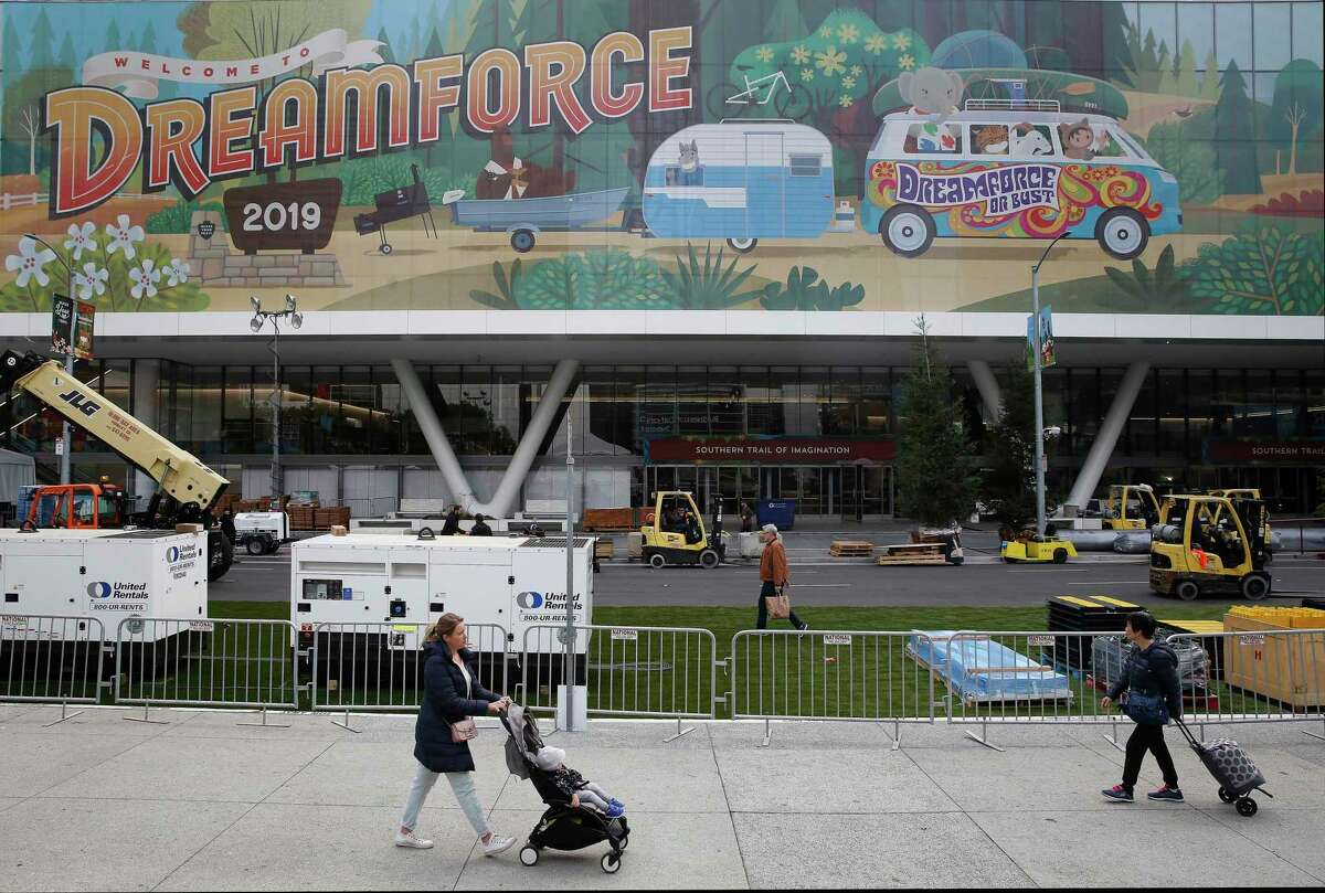 Pedestrians on Howard Street walk past signage for Dreamforce displayed on Moscone Center days before the start of the Salesforce convention in 2019. The festival will be scaled back to just a few hundred people this year.