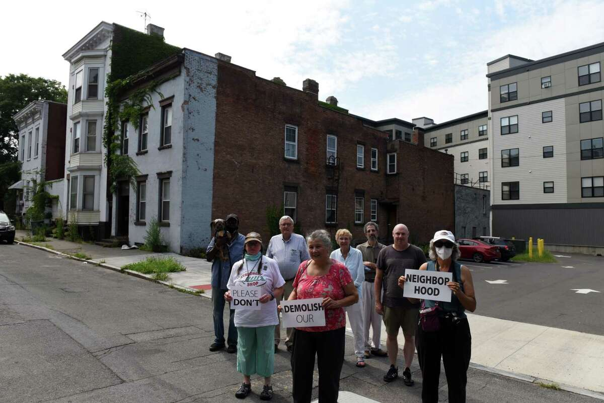 Neighbors from Fifth Avenue between Federal Street and Bethany Baptist Church stand at the location of a proposed apartment complex which they are fighting against on Thursday, Aug. 26, 2021, in Troy, N.Y. The project is pending before the city Planning Commission. The group is looking to protect other downtown locations.