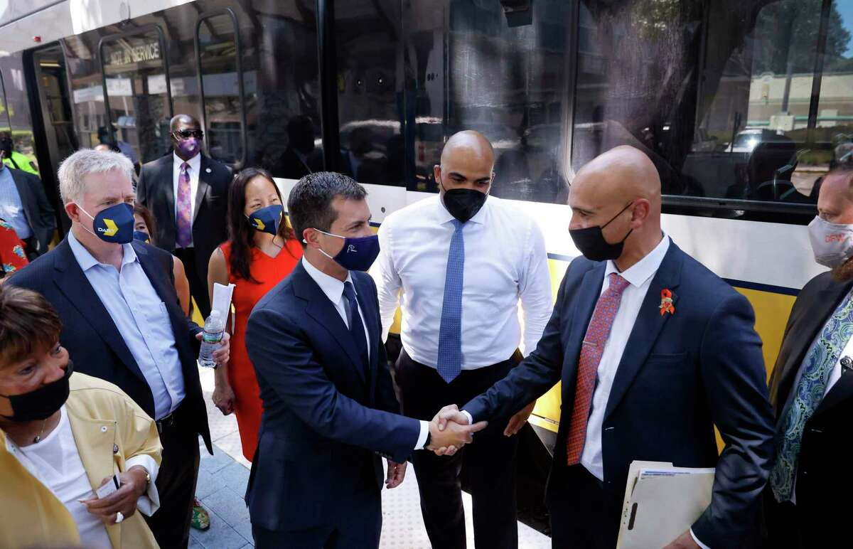 U.S. Transportation Secretary Pete Buttigieg, center, shakes hands with Texas Department of Transportation Dallas District Engineer Mo Bur as they depart a Dallas Area Rapid Transit train at the Lovers Lane station in Dallas on Aug. 11, 2021. Buttigieg toured some of Dallas' transportation sites to see and hear how the Bipartisan Infrastructure Deal's investments in jobs, airports and transit will benefit the area.