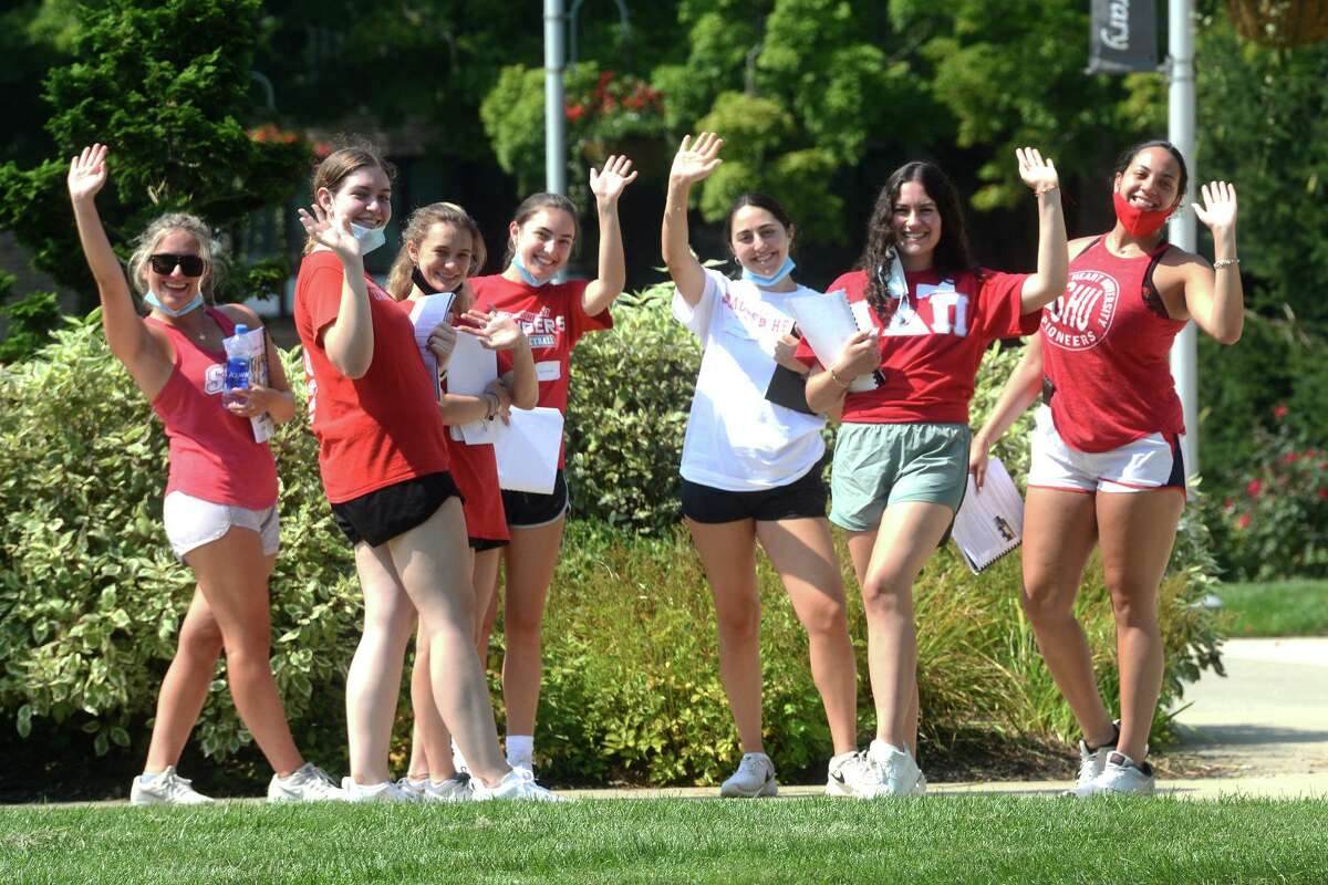 Students wave while taking an orientation tour on move in day on the campus of Sacred Heart University, in Fairfield, Conn. Aug. 26, 2021.