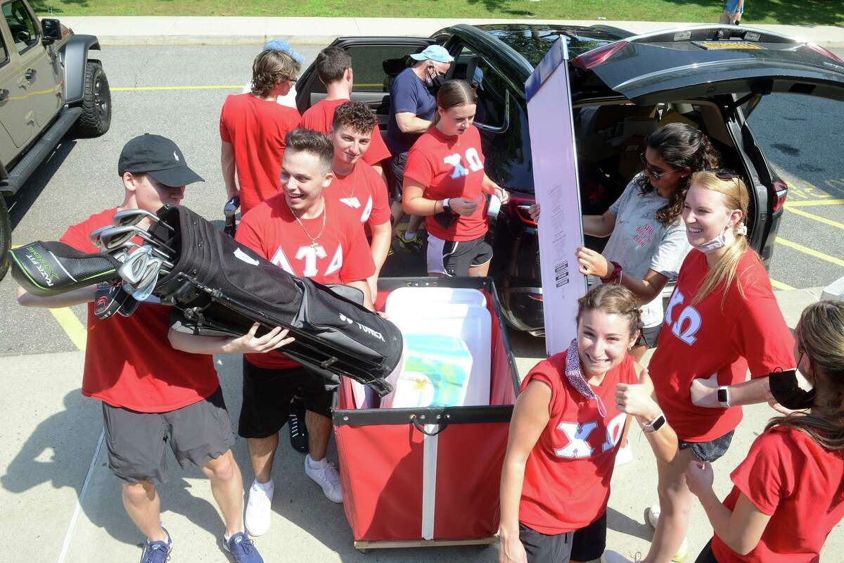 Fraternity and sorority members help first year students move into their dormitories on the campus of Sacred Heart University, in Fairfield, Conn. Aug. 26, 2021.