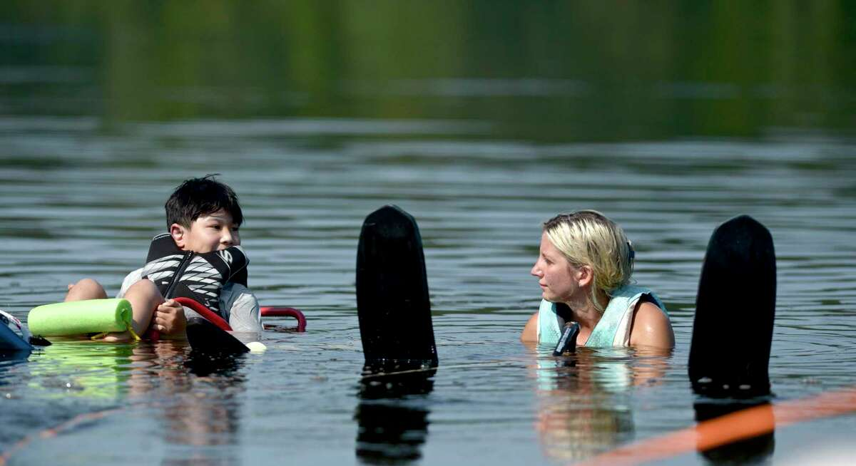 Harry Houng-Lee, 9, of New York City, waits with Cora Fagan, with LOF Adaptive Skiers, to wakeboard.