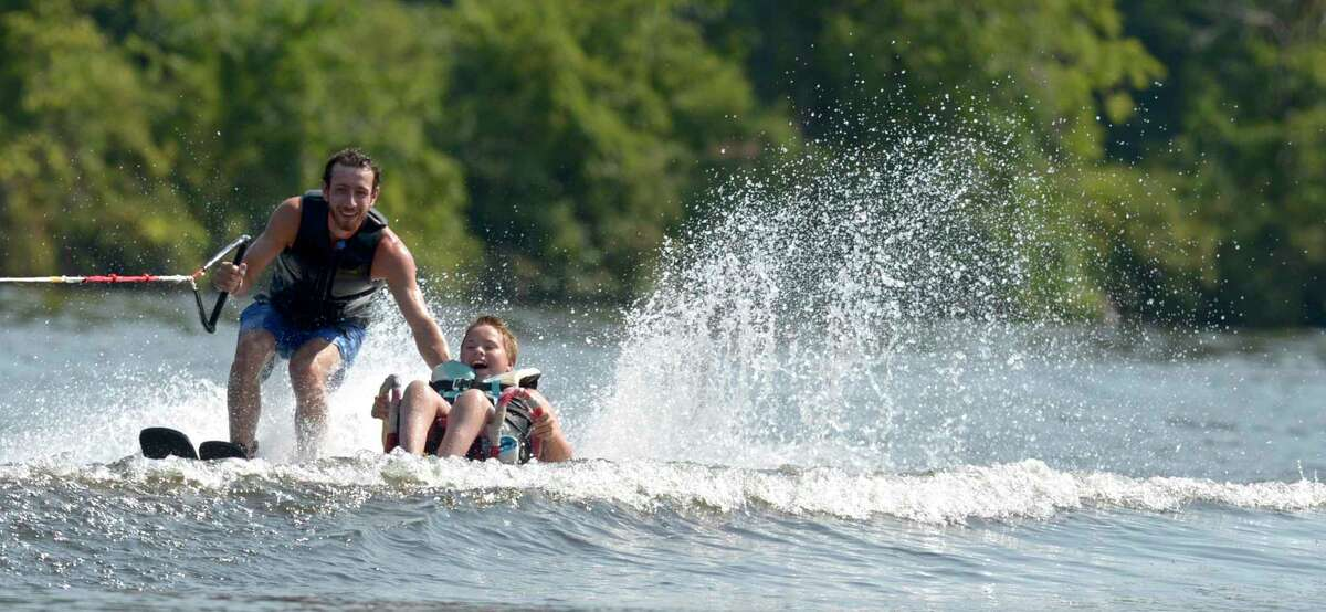 Alex Nowakowski, 12, of Lake Ronkonkoma, N.Y., wakeboards at an HSS Lerner Children's Pavilion adaptive waterskiing event at LOF Adaptive Skiers in Sandy Hook on Thursday. Joey Conrod, with LOF Adaptive Skiers, skis with him.
