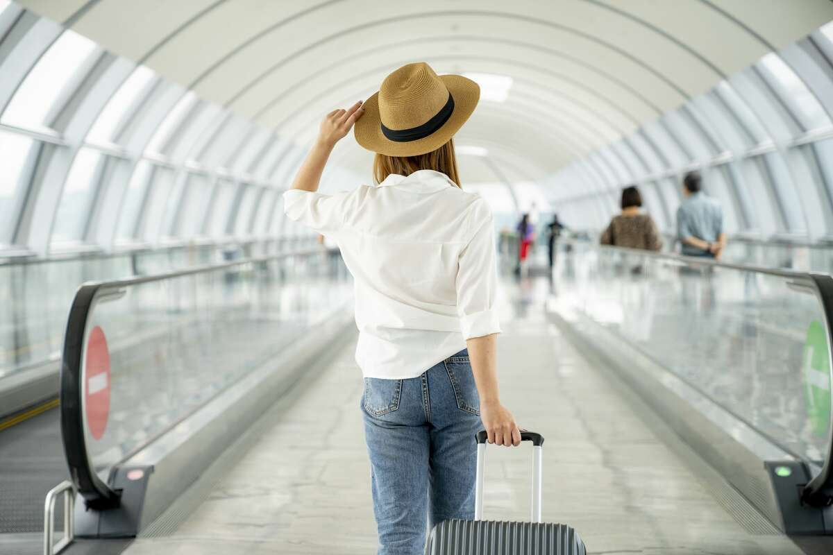 Young casual female traveler with suitcase at airport.