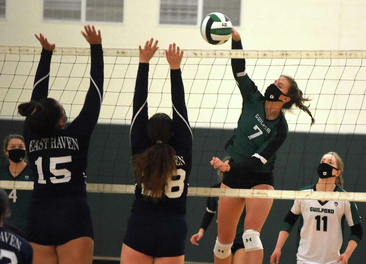 Guilford's Emma Appleman (7) takes a shot as East Haven's Brooke Clancy (15) and Kayla Stefania (28) defend during the SCC Div. C volleyball final in Guilford on Friday, Nov. 13, 2020.