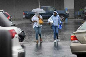 Shoppers brave the rain resulting from Tropical Storm Henri in the Walmart parking lot in Danbury Sunday, August 22, 2021.
