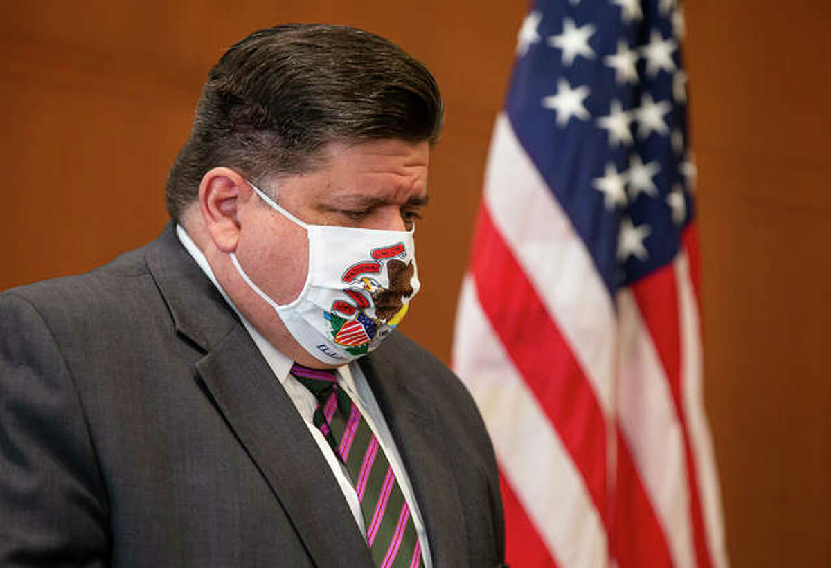 FILE - Gov. J.B. Pritzker appears at a news conference wearing a mask.