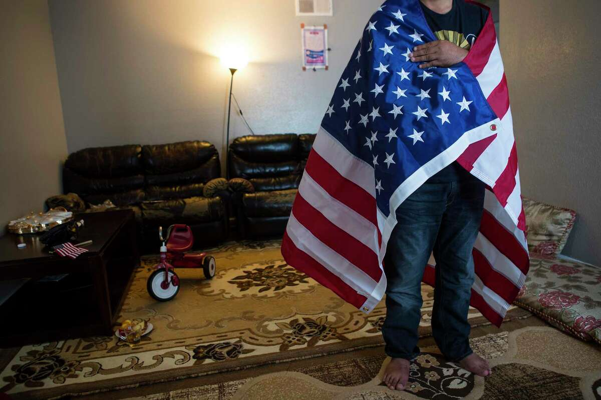 """""""Khan"""", an Afghan Special Immigrant Visa holder, poses for a photo wrapped in an American flag as he speaks about his family's journey fleeing the Taliban in Afghanistan on Monday, Aug. 23, 2021 in Houston. The family arrived safely in Houston Sunday night."""