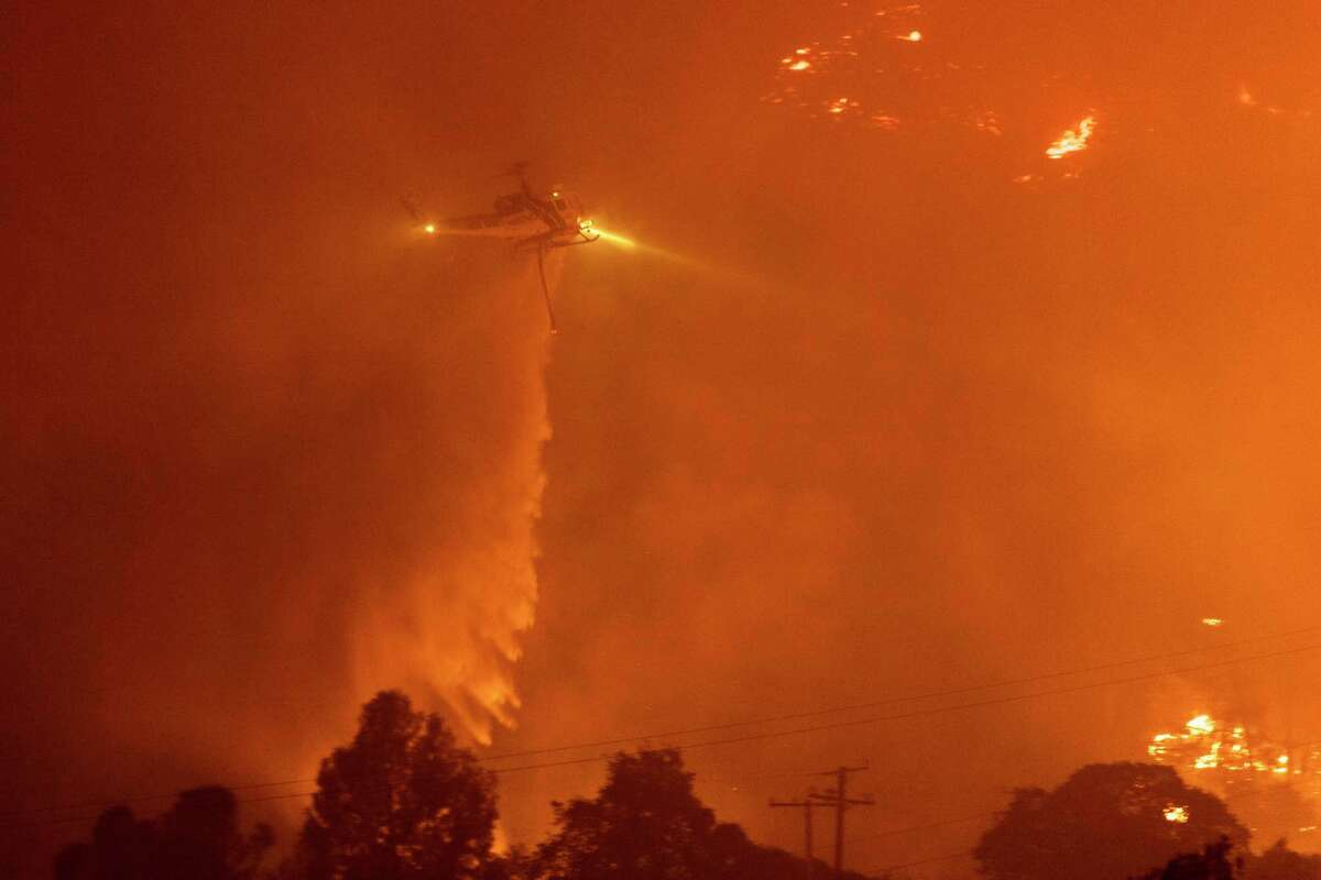 A firefighting helicopter drops water Tuesday on the French Fire over the Kern County community of Wofford Heights.