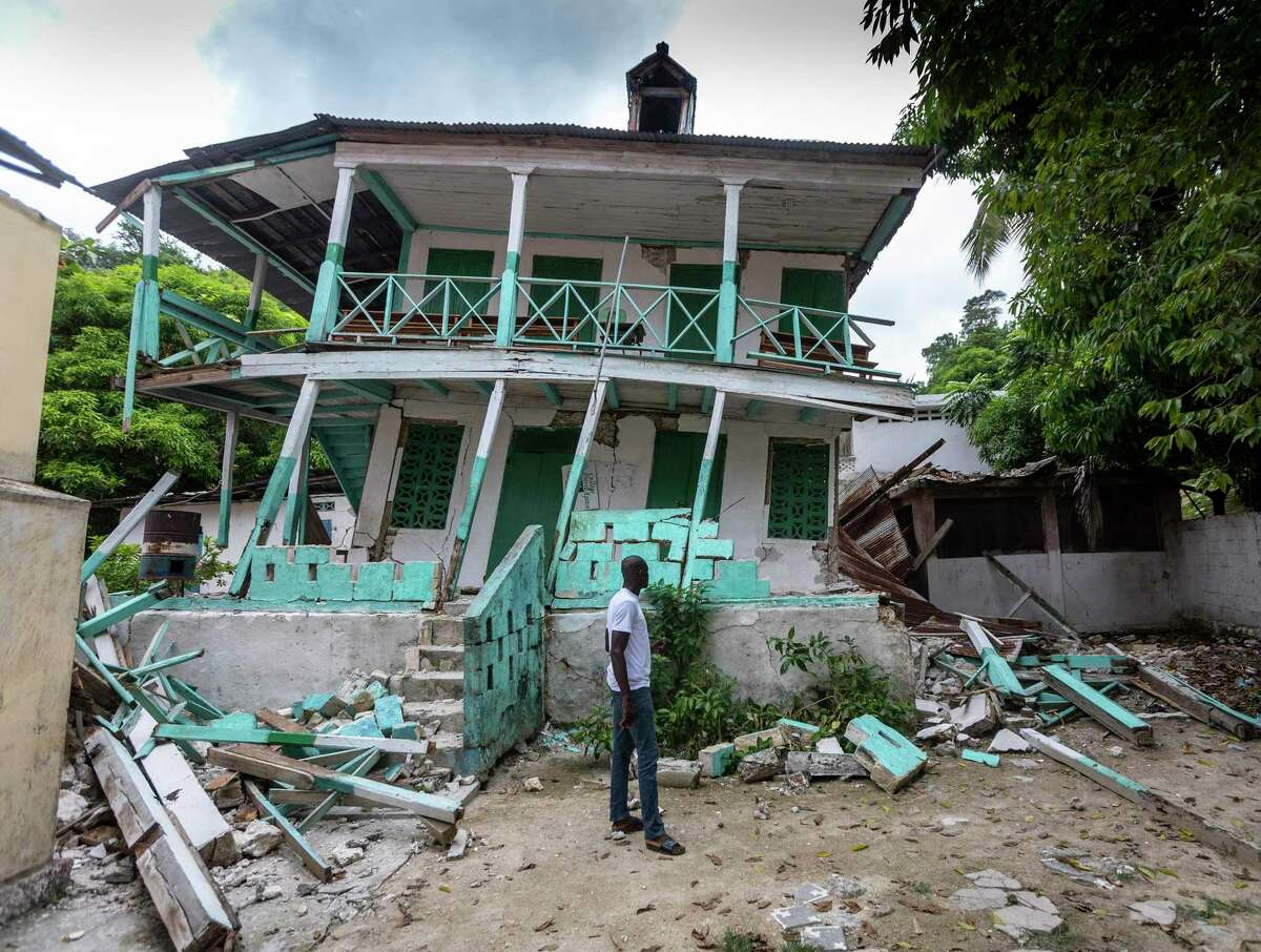 A man stands in front of a damaged school in Corail, Haiti, on August 19, 2021. Many structures in this small fishing village were damaged or destroyed by the earthquake. (Jose A. Iglesias/El Nuevo Herald/TNS)