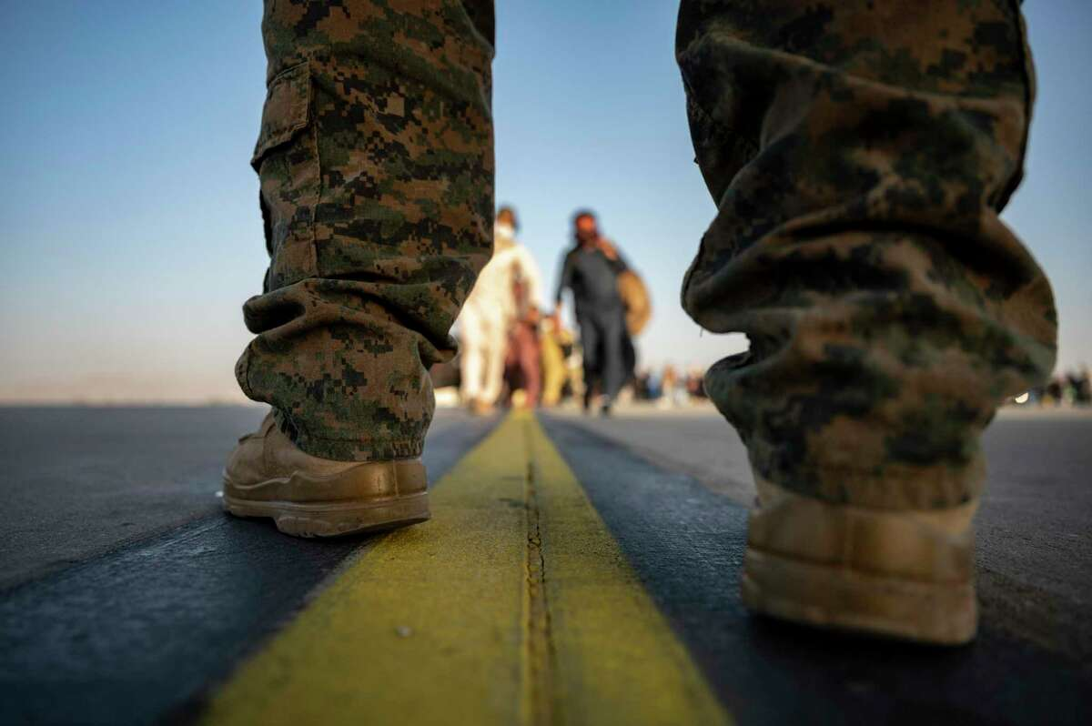 In this image provided by the U.S. Air Force, a U.S. Marine provides security for evacuees boarding a U.S. Air Force C-17 Globemaster III at Hamid Karzai International Airport in Kabul, Afghanistan, Tuesday, Aug. 24, 2021.