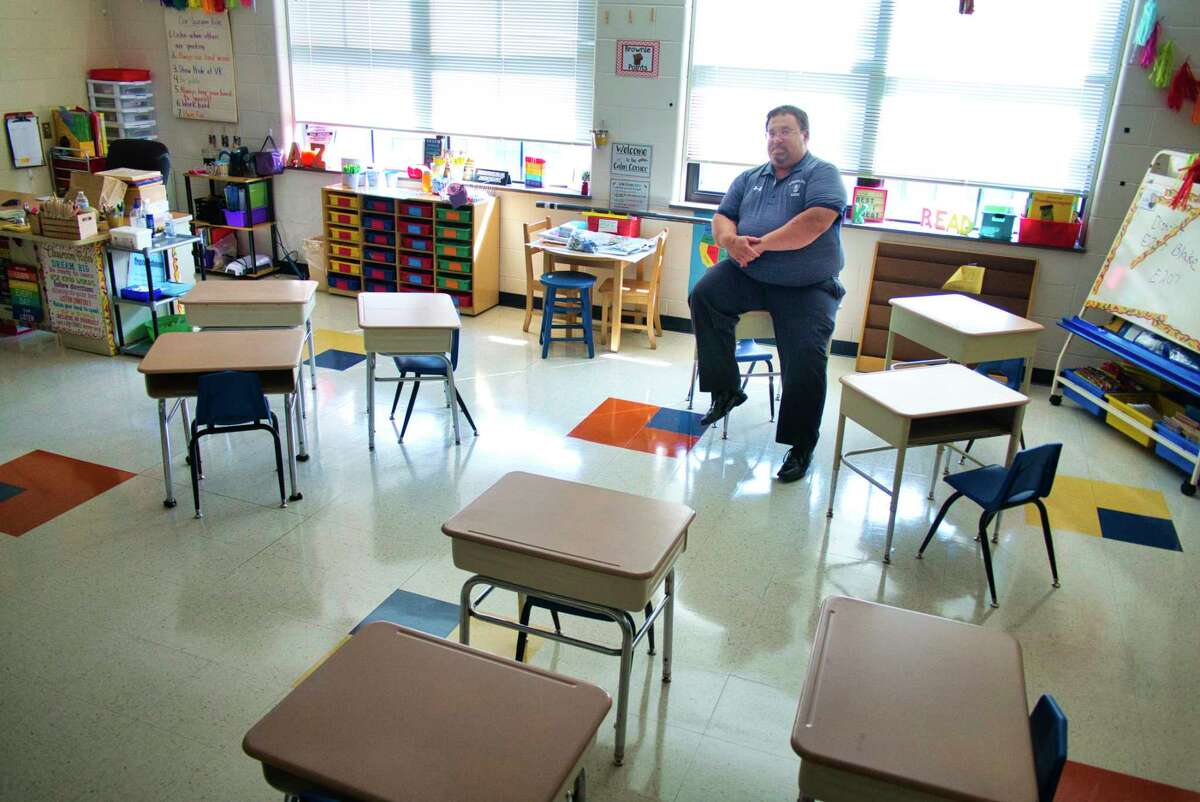 """Rensselaer School District Superintendent Joseph Kardash sits in one of the elementary class rooms on Wednesday, Aug. 25, 2021, in Rensselaer, N.Y. The school has come up with a way to sit children near each other while still keeping each child six feet apart. Arraigning the desks this way allows students to see other students and not having to sit students in separated rows. Kardash said that the school is working hard to not make school just Covid centered. """"School needs to be a welcoming place"""", Kardash said."""
