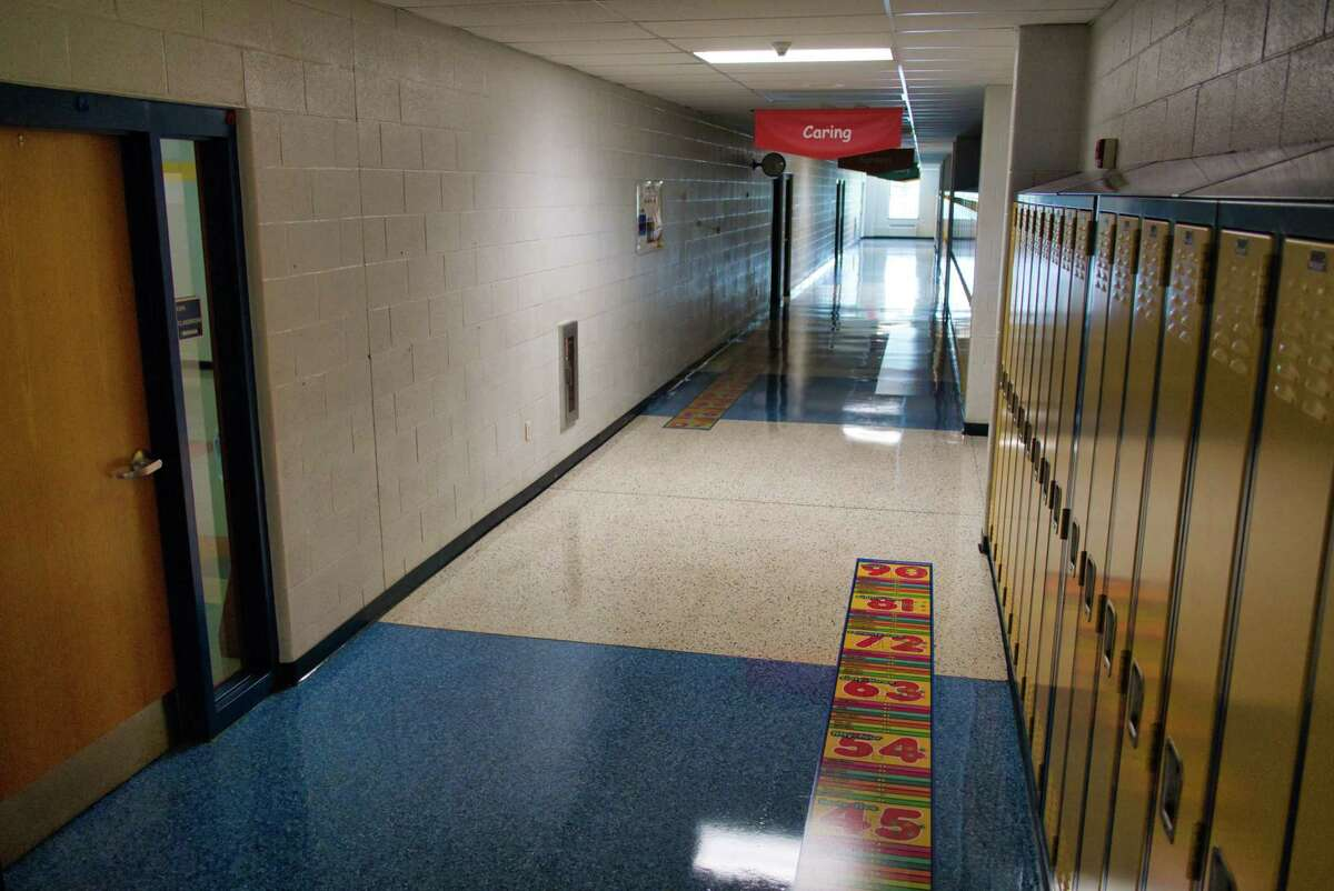 """A view of third floor hallway inside the Rensselaer Junior Senior High School on Wednesday, Aug. 25, 2021, in Rensselaer, N.Y. The school has removed the tape on the floors marking six feet distances and separation lines and instead using thought provoking stickers that are instructional based to keep students apart as they walk through the halls. Superintendent of schools, Joseph Kardash, said that they are using floor sticker and wall signs that are not Covid centered. """"The students have learned from last year how to keep safely apart, they need to be back at a school that is welcoming and not centered on only Covid precautions"""", he said."""